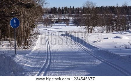 Cross-country Skiing Tracks In Winter Landscape. Buildings In The Background.