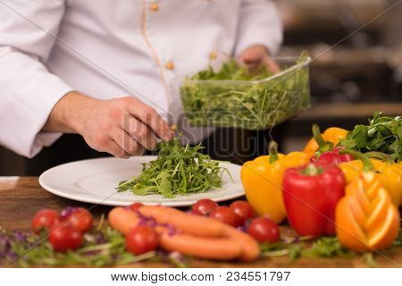 chef serving vegetable salad on plate in restaurant kitchen
