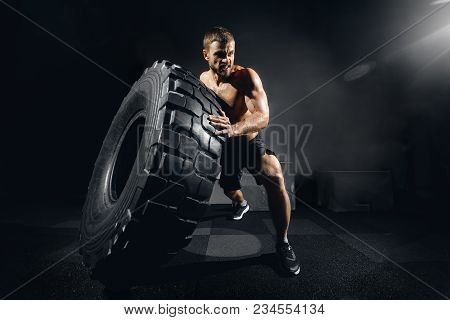 Muscular Fitness Shirtless Man Moving Large Tire In Gym Fitness Center, Concept Lifting, Workout Cro