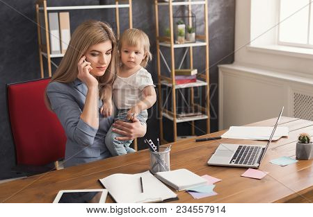 Happy Mother Working At Office With Her Baby. Young Woman Talking On Phone While Spending Time With