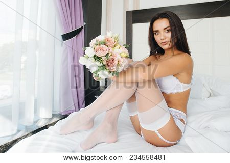 Sexy Young Woman With Straight Body In White Bride Erotic Lingerie. Bride With Make Up And Flash Hai