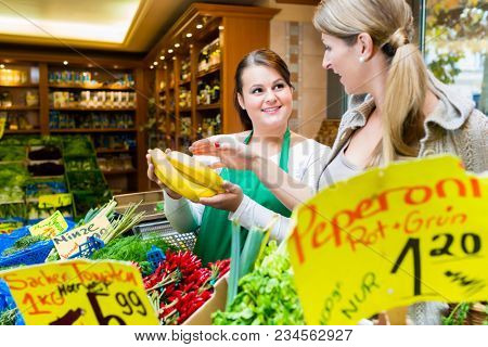 Woman buying banana in fruit grocer store being helped by saleswoman