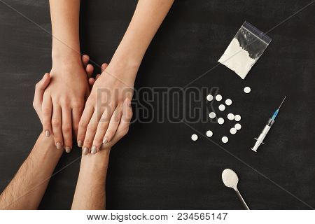 Drug Addict Hands Asking For Help On Dark Table With Cooked Heroin, Pills, Spoon And Plastic Bag. Co
