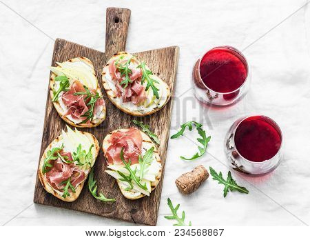 Bruschetta With Cream Cheese, Pear, Prosciutto, Arugula On Wooden Chopping Board And Red Wine  On Li
