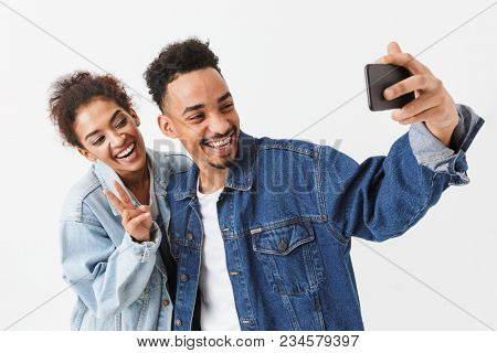 Smiling african couple in denim shirts having fun together while making selfie on smartphone over grey background