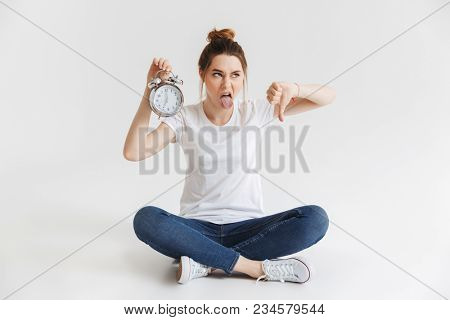 Portrait of an upset young girl holding alarm clock and showing thumbs down while sitting with legs crossed isolated over white background