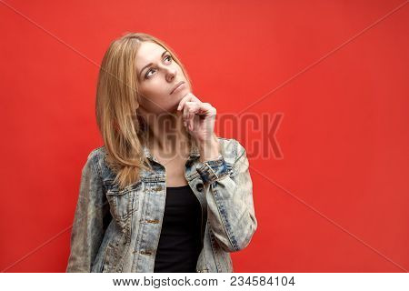 Stylish Attractive Slender Young Blonde Student Woman Thoughtfully Holds Her Chin And Looks Up With
