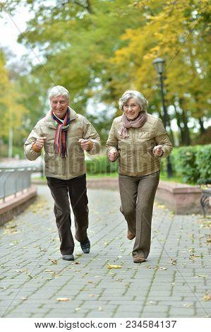 Portrait Of Beautiful Caucasian Senior Couple Running In Park