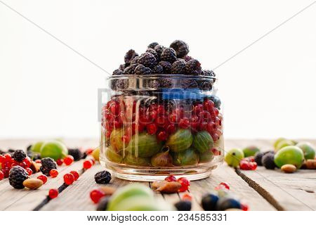 Forest Berries Stacked In Layers In A Glass Jar. Red Currants, Black Currants, Blackberries, Goosebe