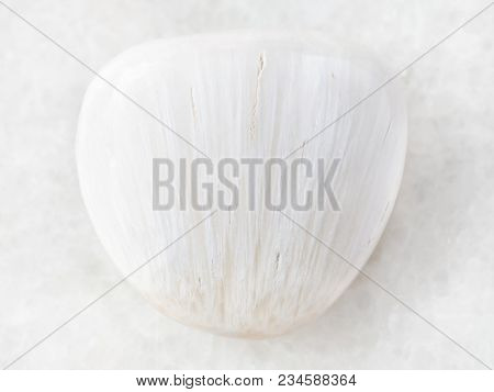 Macro Shooting Of Natural Mineral Rock Specimen - Tumbled Scolecite Gemstone On White Marble Backgro
