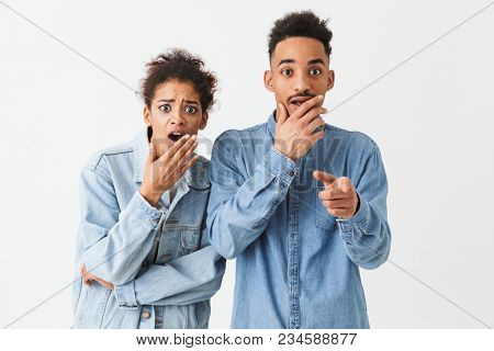Shocked african couple in denim shirts covering their mouths while looking at the camera over grey background