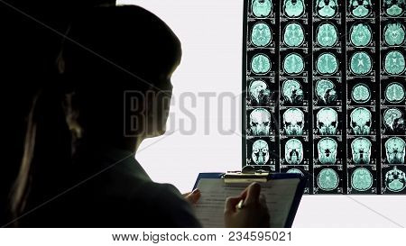 Female Neurologist Looking Thoughtful At Brain X-ray, Writing Down Diagnosis, Stock Footage