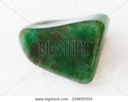 Macro Shooting Of Natural Mineral Rock Specimen - Tumbled Green Aventurine Gem Stone On White Marble