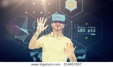 3d technology, virtual reality, cyberspace, entertainment and people concept - happy young man in virtual reality headset or 3d glasses playing game with screens projection over black background