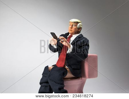 APR 3 2018: Caricature of United States President Donald Trump sitting on a toilet with a mobile phone, Tweeting. Executive Time concept