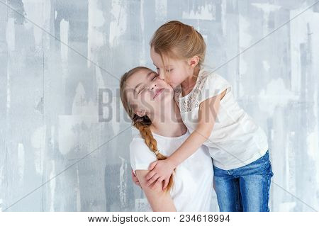 Two Happy Kids Standing Against Grey Textured Wall Background And Embracing. Adorable Pretty Little