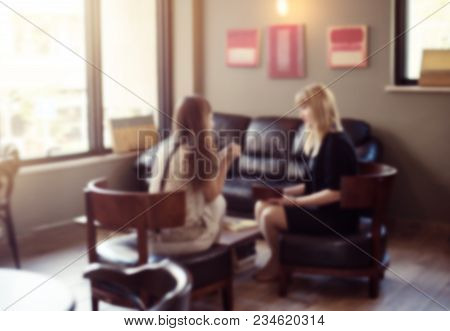 Psychologist Consulting A Woman Client Indoors Discussion Therapy, Blurred Defocused View Two Women