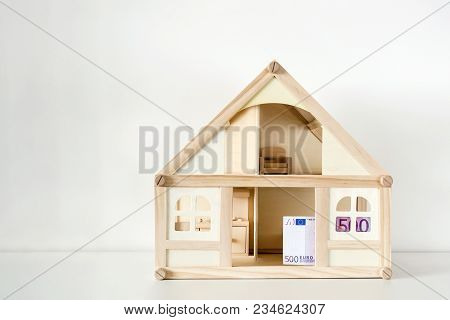 Wooden House Model With 500 Euro Bill. House Rental And Sale. Expenses And Costs For House Handling.