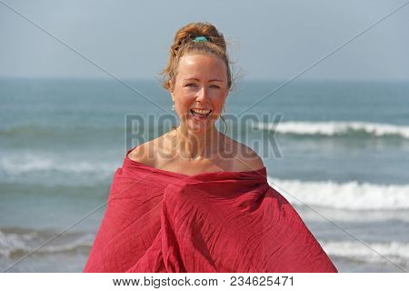 Beautiful Girl With Blond Hair, In A Red Dress On The Background Of The Sea. Summer Girl On The Sea.