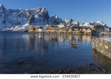 Fishermen Cabins Or Rorbuer, Mountains And Water At Sikrisoya, Lofoten, Norway