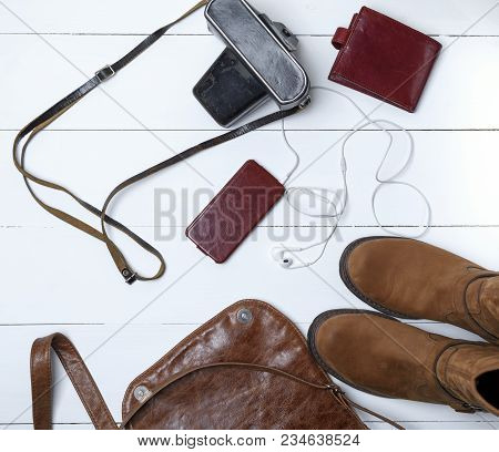 Leather Brown Boots, Smartphone In A Case With Headphones, Purse And Old Vintage Camera In A Black C