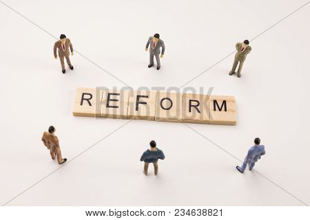 Miniature Figures Businessman : Meeting On Reform  Letters By Wooden Block Word On White Paper Backg