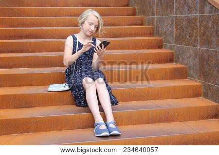 Stylish Preteen Girl Using A Phone Sitting On A Rusty Staircase In A Modern Building. Child And Gadg