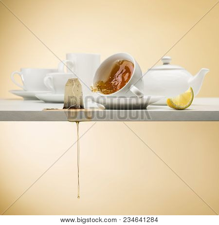 Falling Cup Of Tea On White Table With Tea Bag Dripping And Lemon Slice
