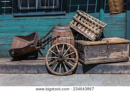 Western Chariot S Wheel, Wooden Wheelbarrow, Cask And Boxes In The Street.