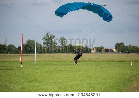 Parachutist With Blue Parachute Near To The Ground Preparing For Landing.