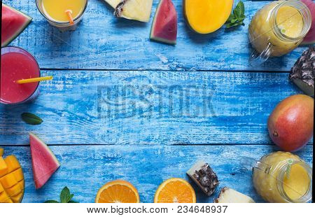 Fresh Pineapple, Mango And Watermelon Cocktail In Two Glasses With Fruits On A Blue Wooden Rustic Ba