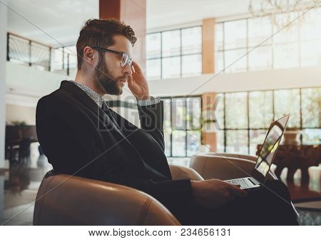 Portrait Of A Serious Concentrated Bearded Handsome Man Entrepreneur In A Formal Suit Adjusting His