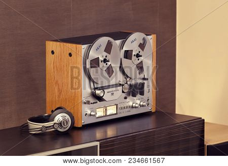 Vintage Open Reel-to-Reel Tape Deck Stereo Recorder with Headphones Side Angled View
