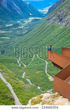 Travel Concept. Tourist Woman Looking At Trolls Path Trollstigen Or Trollstigveien Winding Scenic Mo