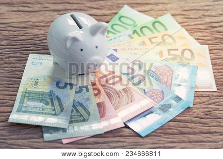 White Piggy Bank On Pile Of Euro Banknotes On Wooden Table, Financial Savings Money Account Or Europ