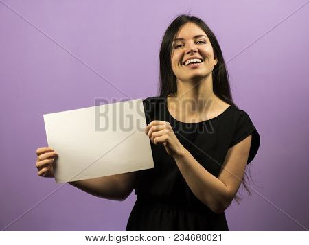 Surprised Young Brunette Girl Smiling While Holding Empty Blank White Copyspace Sheet . Leaflet Pres