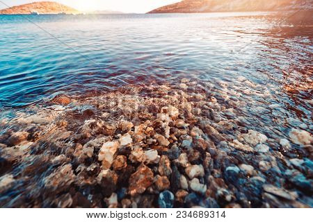 Beautiful view of pebbles bottom under clear transparent water of Mediterranean sea near Greek island, summer vacation on the beach