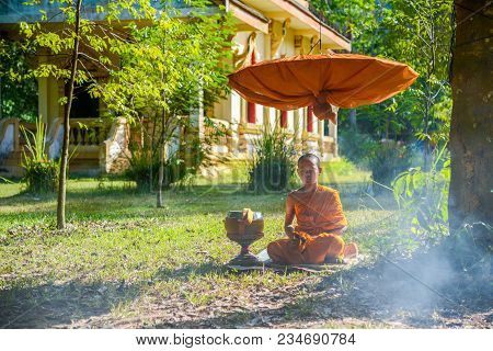 Krabi, Thailand - May 2, 2015: Novice Monk Meditating On Field Under Long-handled Umbrella Close To
