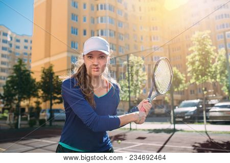 Woman , Looking At Camera And Holding Tennis Racket. Attractive Tennis Player Playing Tennis Outdoor
