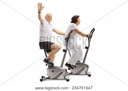 Elderly man and an elderly woman riding exercise bikes with the man waving at the camera isolated on white background