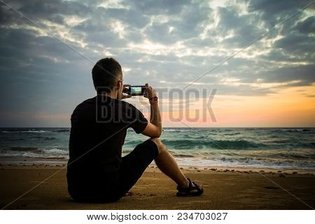 A Man Sits On The Sand And Takes Video As The Sun Rises From The Horizon To The Sea. Man Taking Phot