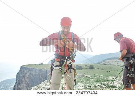 Two Man Rock Climbers Climbed On The Cliff. Happy Climbers On The Top Of The Mountain.
