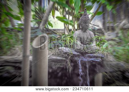 Peaceful And Spiritual Grey Stone Buddha Searching For Enlightenment With Mini Waterfall, Natural Pl