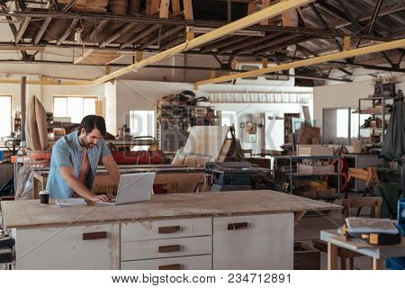 Skilled Young Woodworker Standing At A Workbench In His Large Carpentry Studio Full Of Carpentry Equ