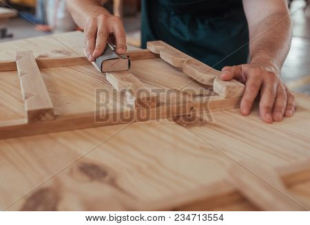 Closeup Image Of A Skilled Woodworker Hands Sanding Pieces Of A Wooden Furniture Design While Workin