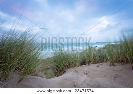 Waves Crashing In Sea On Windy Cold Day With View Between Long Grasses In Sand Dunes At Hayle Beach,