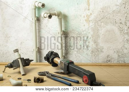 Soldering Iron For Plastic Pipes On Wooden Table On Old Wall Background. Equipment For Plumbing Work