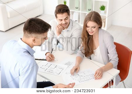 Real estate agent showing plan of apartment to clients in office