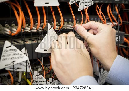 Close-up Of Engineer's Hand With Optical Patch Cord Is Connected To Switch. Setting Up Data Center E