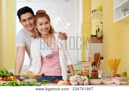 Portrait Of Happy Hugging Young Asian Couple Standing In Kitchen